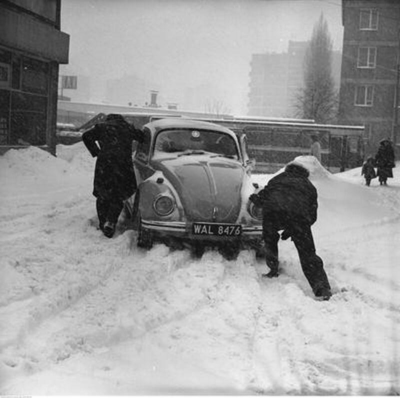 Mężczyźni pchający samochód Volkswagen Garbus